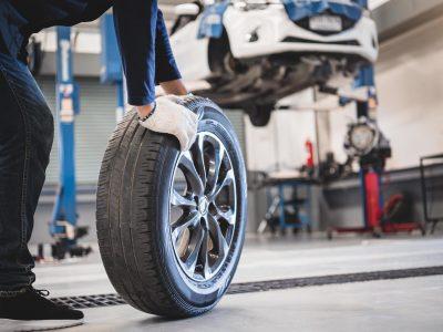 male-mechanic-rolling-tire-free-photo